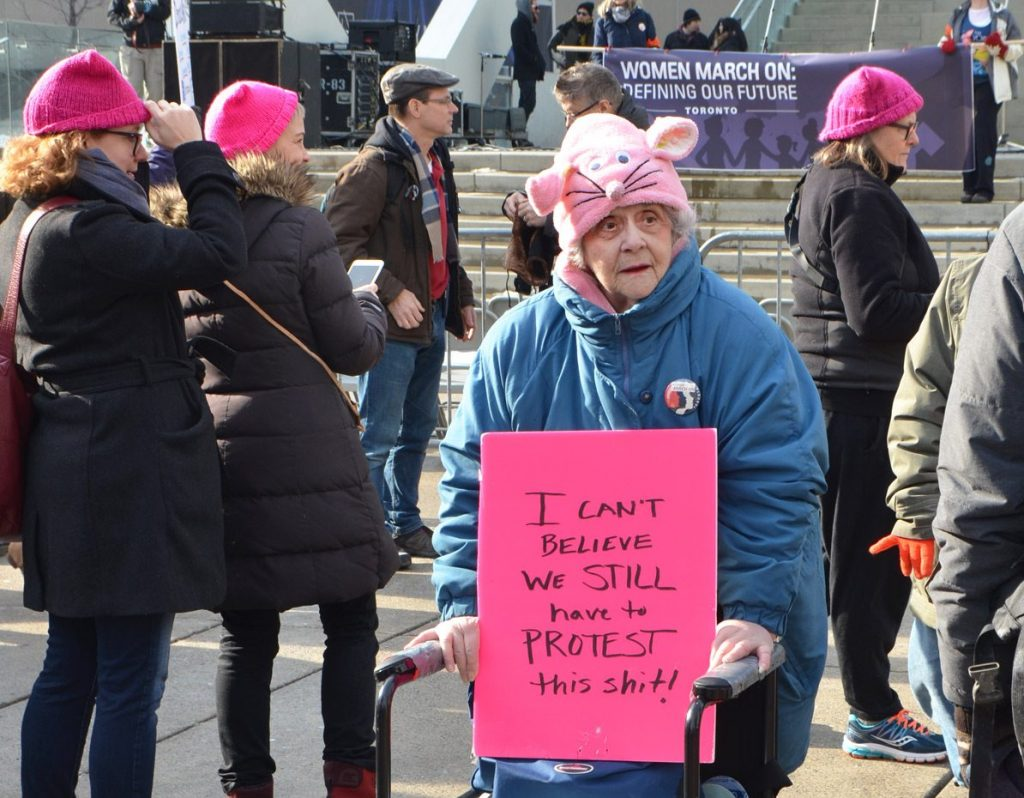 An older woman at a demonstration walking with a wheelchair and wearing a pink hat